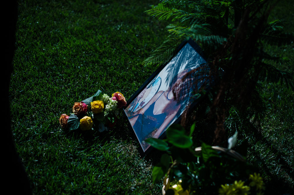 A portrait of Rosie and some flowers next to her grave at her funeral.