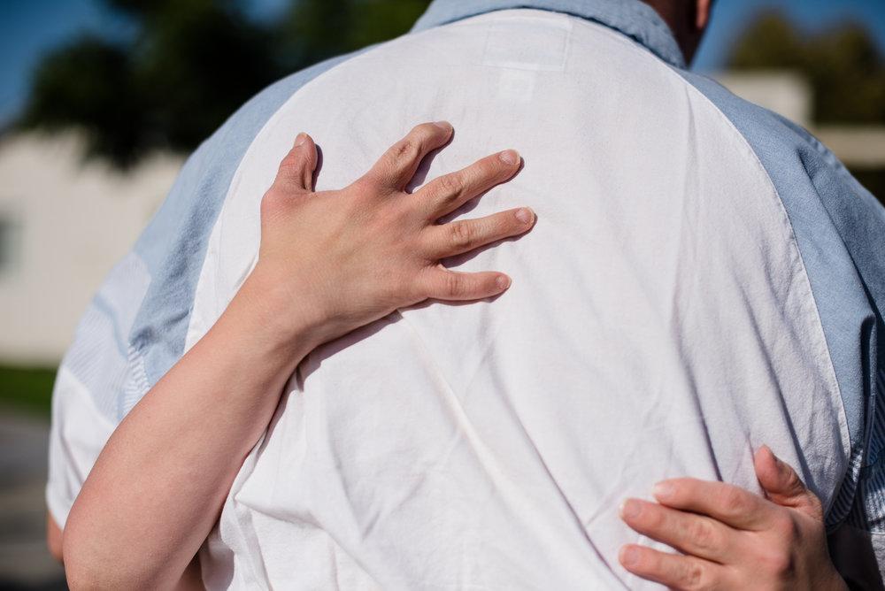 Krysta grips Nathaniel's back.