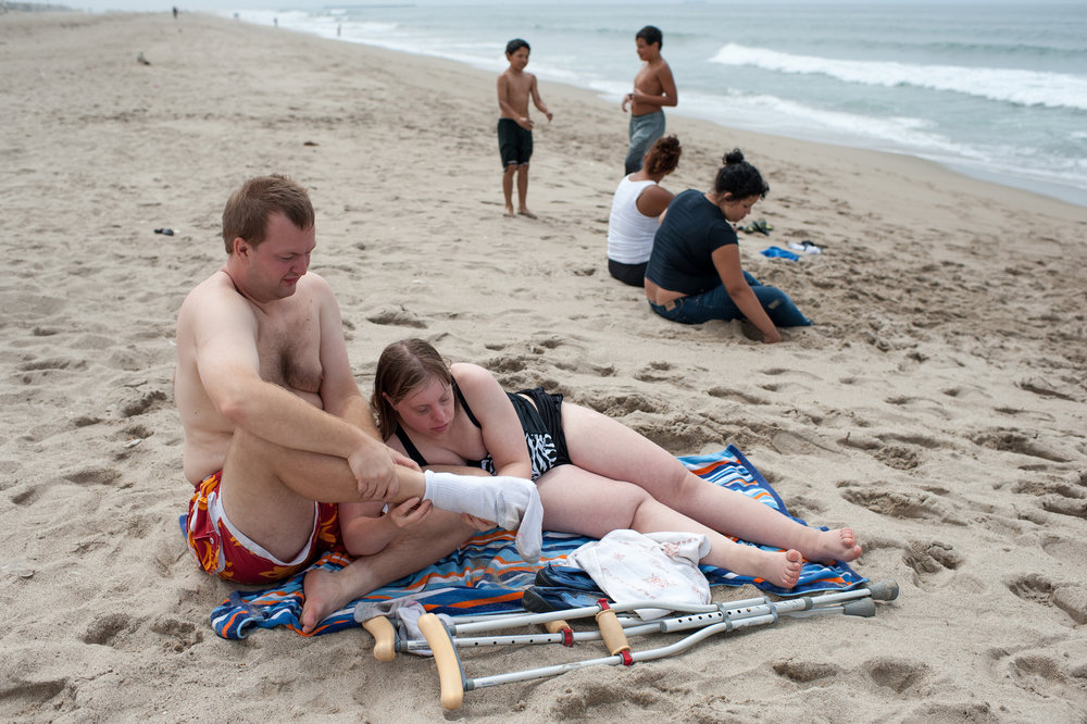 Krysta removes Nathaniel's sock at the beach during an outing in Ventura, California.