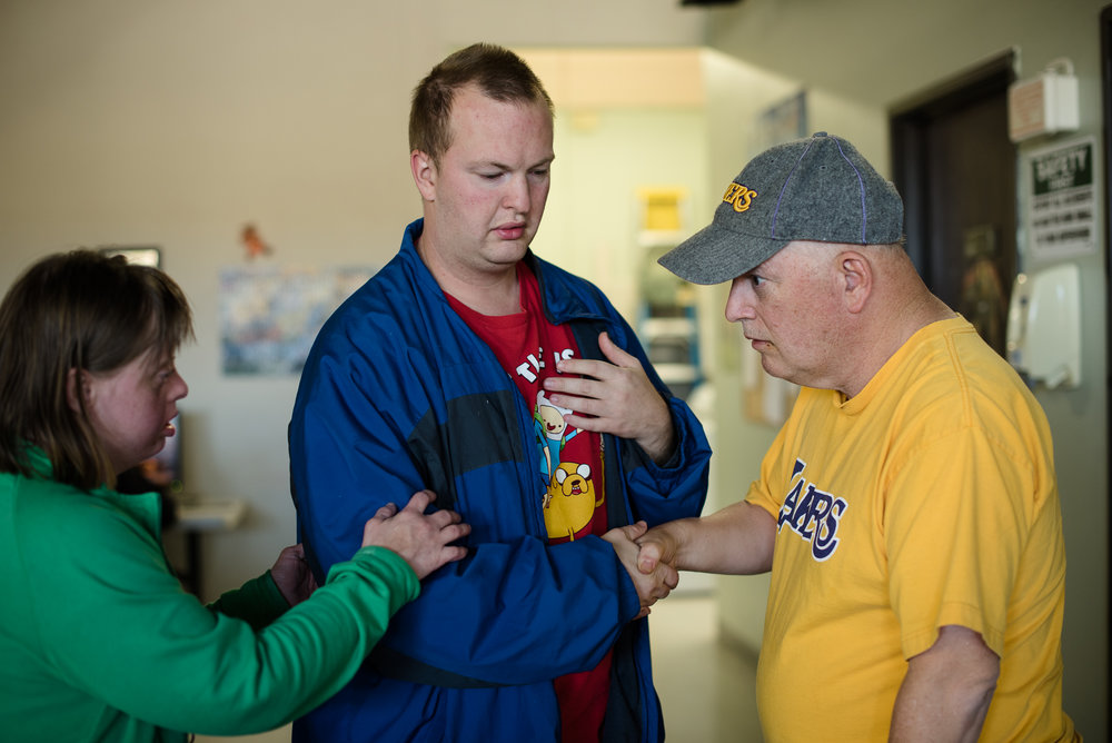Nathaniel shakes hands with Gary, a participant of the workshop, after an argument, while Krysta holds Nathaniel's arm in support.