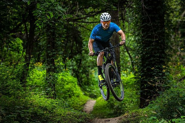 XC racer David Archer catching just a little air, but with style! This looks like the jungle, but it's actually just Missouri in summer.  @ridecannondale @cannondalemountain #ridelefty #ridescalpel #ridecannondale  #xcracer @oakleybike @oakley #frogskins #singletrack #mtb #castlewood #stingingnettles #missourimtb @the_cyclerys @thecyclerys #thecyclerysraceteam