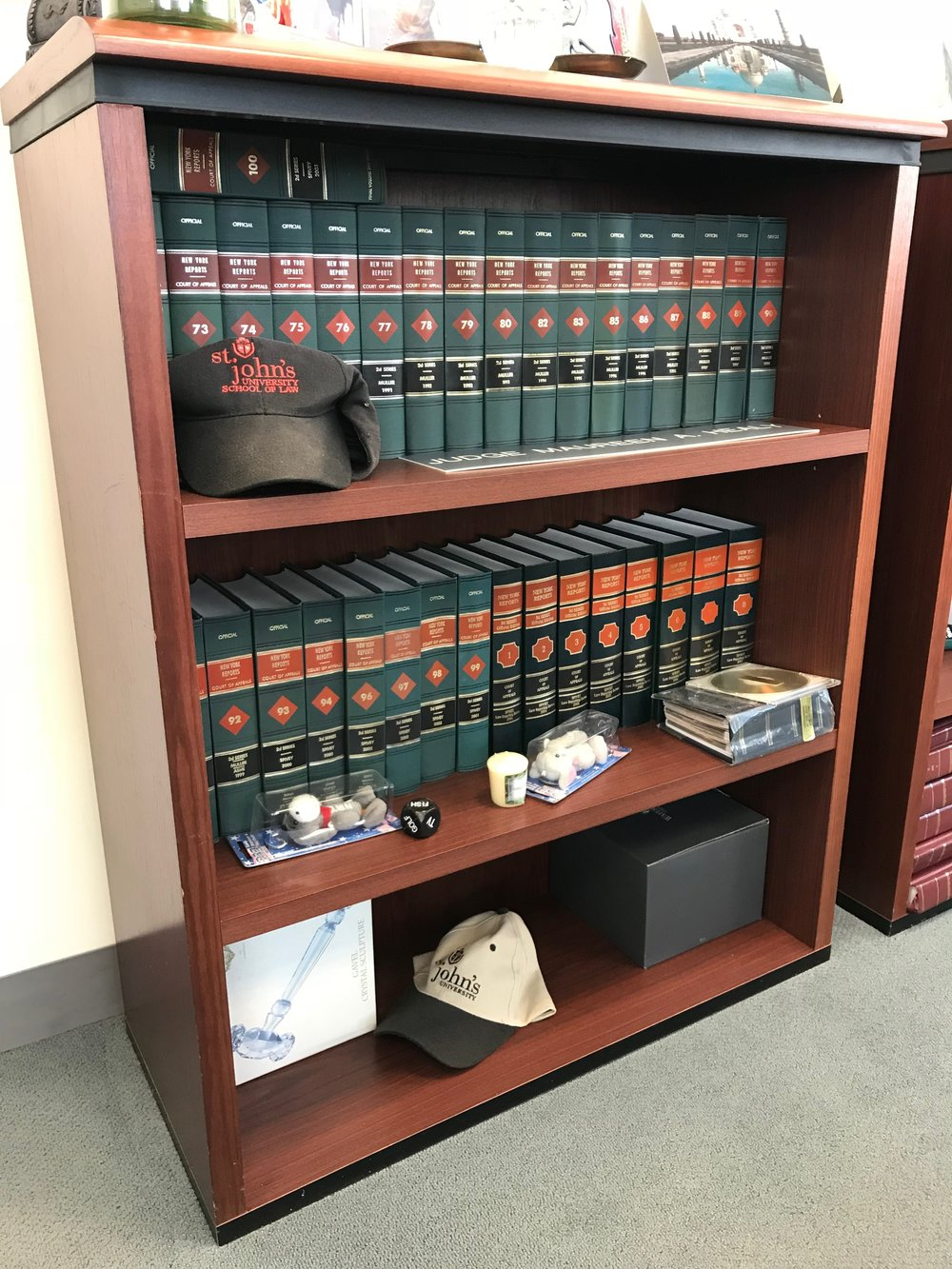 St. John's caps sit on the shelf among Healy's legal tomes. //  Eagle  photo by David Brand