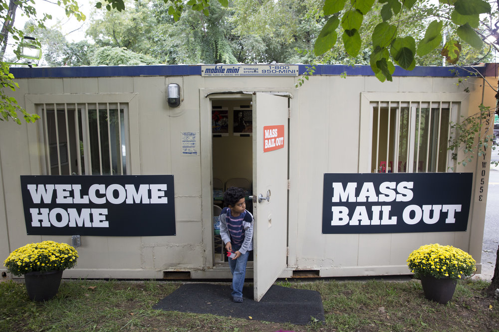 A child stands in the doorway of the Mass Bail Out Welcome Station Trailer. //  Eagle  Photo by Clarissa Sosin