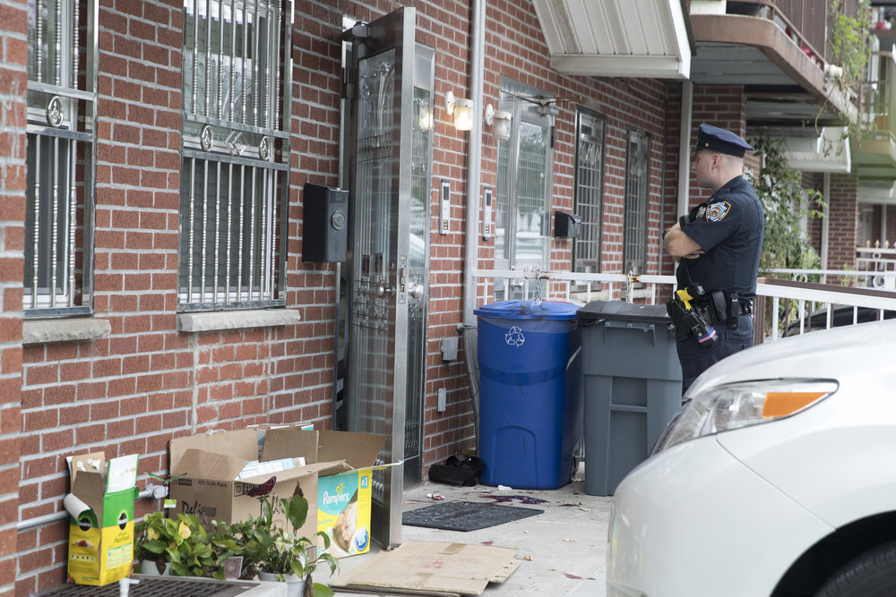 A police officer stands guard at the house were five people were stabbed overnight is seen, Friday, Sept. 21, 2018, in New York. Police say five people, including three infants, were stabbed at an overnight day care center in New York City. (AP Photo/Mary Altaffer)