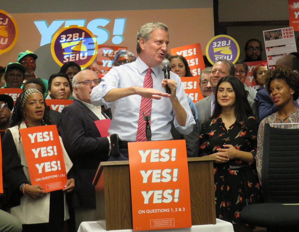Mayor Bill de Blasio urges New Yorkers to flip their ballot in order to vote in favor of three charter revision ballot proposals as Queens State Senate candidate Jessica Ramos (right of de Blasio) looks on. //  Eagle  photo by David Brand