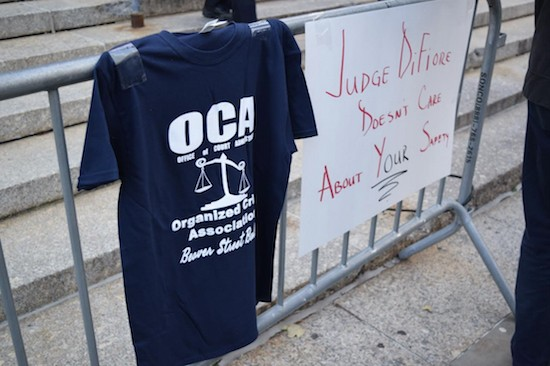 A navy blue t-shirt designed by members of the state's Court Officers Association hangs on a barricade outside of 60 Centre St. in Manhattan during a protest on Oct. 23, 2018.  Eagle  photo by Christina Carrega.