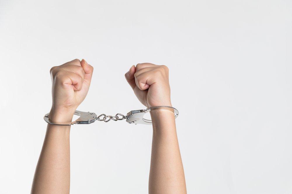 Person showing handcuffs. Photo by Niu Niu courtesy of Unsplash.