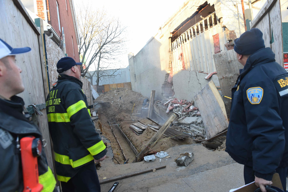 FDNY and Buildings officials watch as a wall collapses.