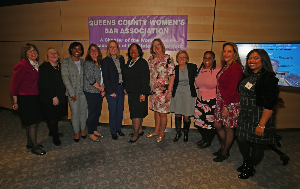 Officers and members of the Queens County Women's Bar Association pose with Queens Borough President Melinda Katz (5th from left), QCWBA President Adrienne Williams (center) and State Delegate Louise Derevlany (5th from right).