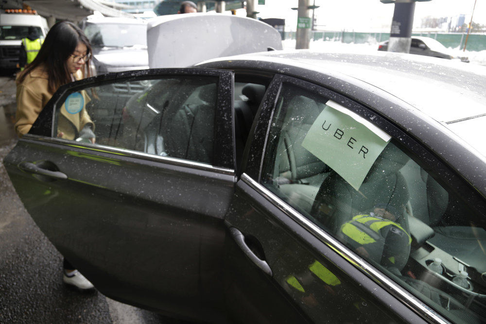 In this March 15, 2017, file photo, a passenger enters an Uber car at LaGuardia Airport in New York. (AP Photo/Seth Wenig, File)