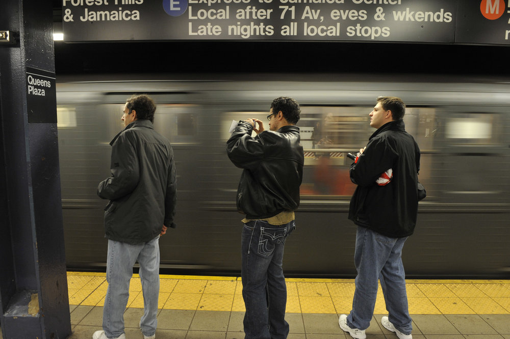 Commuters wait for a train at Queens Plaza. Photo via the MTA.