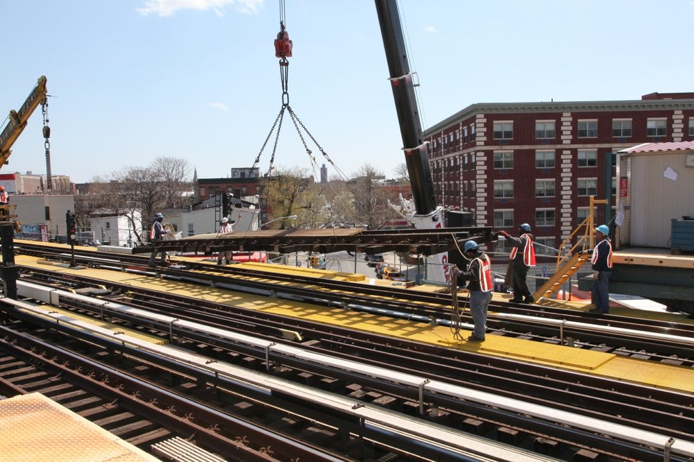 An old panel is hooked up to crane for removal during maintenance work along the J line in 2014. Photo via MTA New York City Transit / Leonard Wiggins.