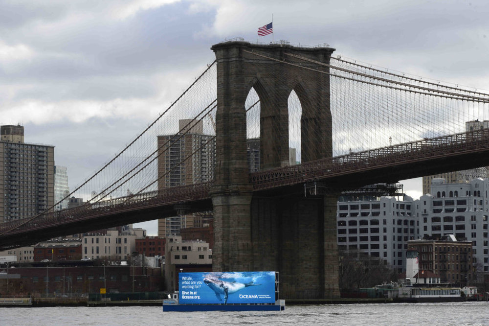 A 60-foot-wide advertising barge with a 20-foot high screen, roaming the East River and New York Harbor, has created an uproar from residents and politicians.  Eagle  photos by Todd Maisel.