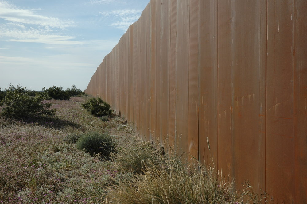 A partial border wall separates the U.S. and Mexico in the Sonora Desert. Photo by Wonderlane/Flickr