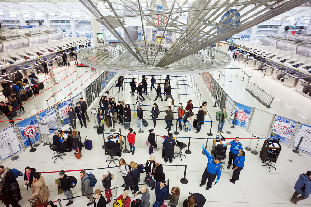 Passengers stand in line as they wait to pass through a TSA security checkpoint at JFK International Airport