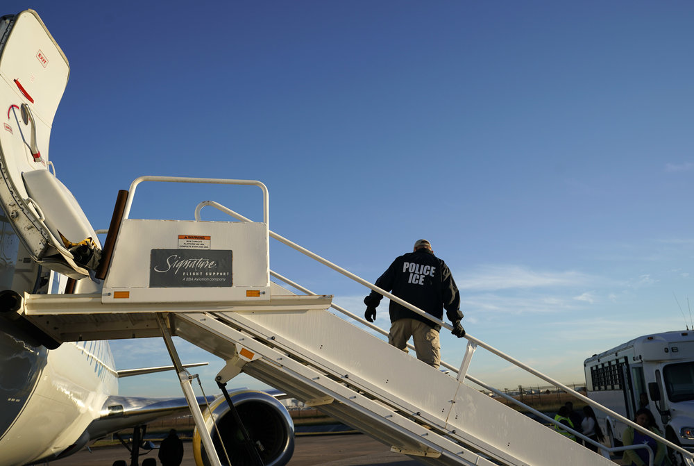 An officer watches as immigrants who entered the United States illegally are deported on a flight to El Salvador by U.S. Immigration and Customs Enforcement. (AP Photo/David J. Phillip)