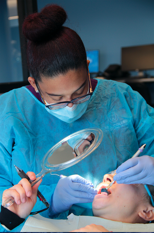 A hygienist cleans on a young person's teeth. Photo courtesy of Plaza College