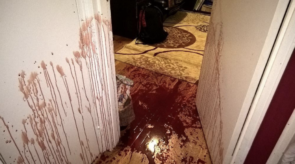 A crime scene photo introduced into evidence shows a blood-stained wall and floor inside the apartment Larrea and Barba shared. Photo courtesy of the Queens District Attorney's Office.