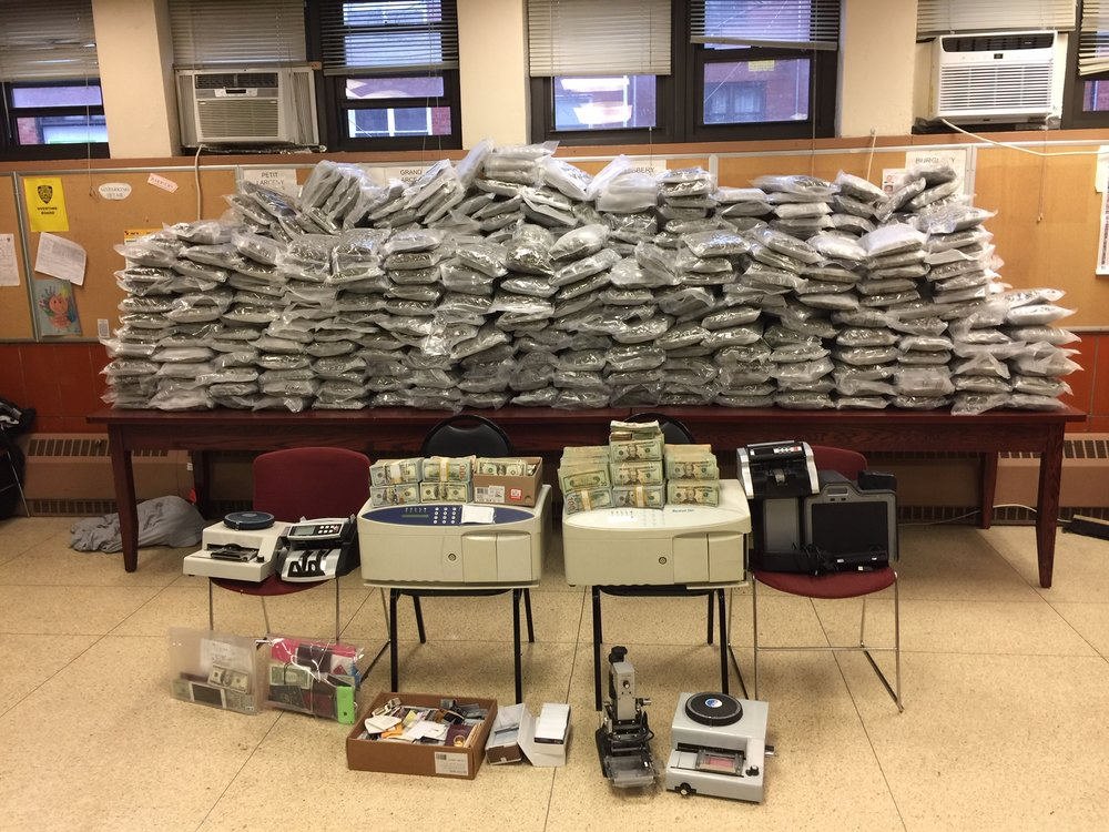 Police recovered $600,000 in cash and 480 one-pound packets of marijuana from a home in Flushing, where three defendants allegedly made counterfeit credit cards. Photo courtesy of the Queens DA's Office.