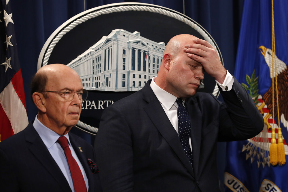 Acting Attorney General Matt Whitaker (right) wipes his brow Monday after announcing an indictment on violations including bank and wire fraud of Chinese telecommunications companies including Huawei at the Justice Department in Washington. At left is Commerce Secretary Wilbur Ross. AP Photo/Jacquelyn Martin.