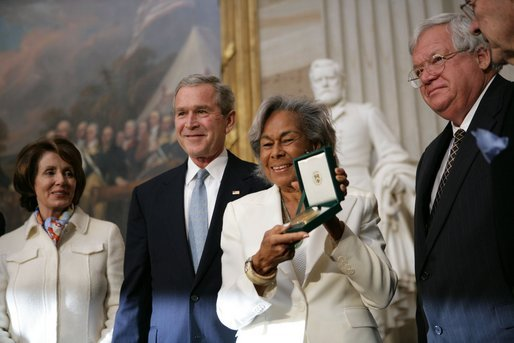 Rachel Robinson (holding award) accepts the posthumous Congressional Gold Medal for her husband from President George W. Bush in a March 2, 2005, ceremony in the Capitol Rotunda. Also pictured are Nancy Pelosi and Dennis Hastert. Photo via the White House.