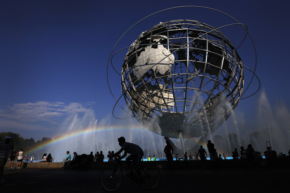 A cyclist passes under a rainbow at the Unisphere fountain inside Flushing Meadows Corona Park.