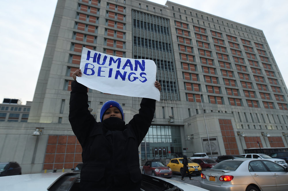A demonstrator holds a sign in support for the detainees inside MDC.  Eagle  photo by David Brand.