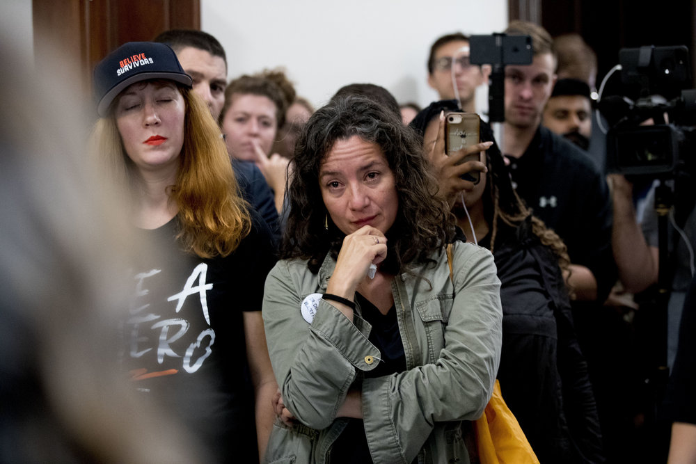 Ana Maria Archila becomes emotional as protesters tell their personal stories of sexual assault outside the office of former U.S. Sen. Jeff Flake before the vote on Supreme Court nominee Brett Kavanaugh on this Sept. 24, 2018. Archila was invited to the State of the Union as a guest of U.S. Rep. Alexandria Ocasio-Cortez. AP Photo/Andrew Harnik.