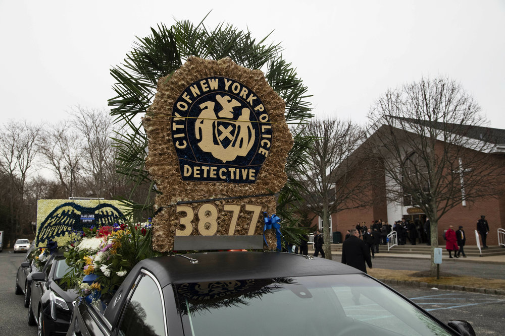 A limousine from the funeral procession for Det. Brian Simonsen, is parked in front of the Church of St. Rosalie in Hampton Bays, NY on Wednesday. AP Photo/Mark Lennihan.