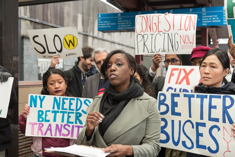 Natasha Saunders of Riders Alliance spoke to commuters and advocates at a rally to pass congestion pricing outside of Jamaica Center.