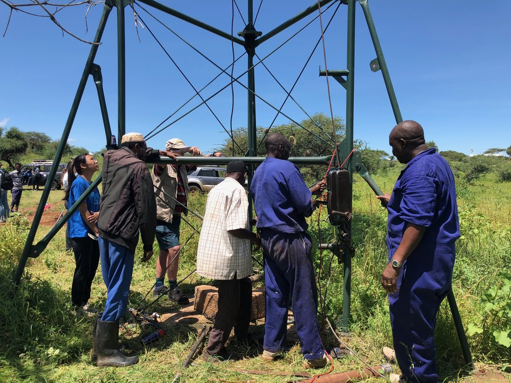 Team members working with village leaders and employees of Kijito Windmill to assess the cause of the broken windmill.