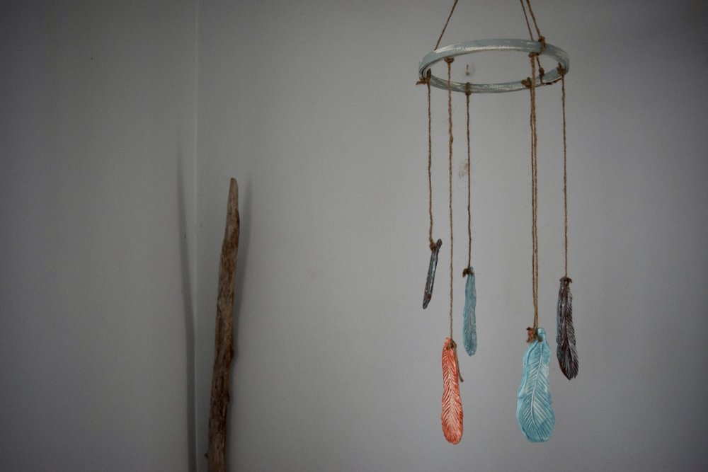 One of our beautiful, one of a kind items available in our etsy shop features hand sculpted feathers strung from natural twine suspended from a vintage painted embroidery hoop.