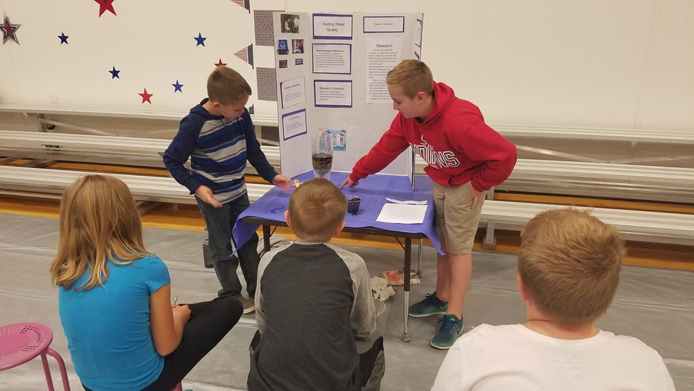 Student Environmentalists are presenting their research about water quality to an audience of fourth graders.