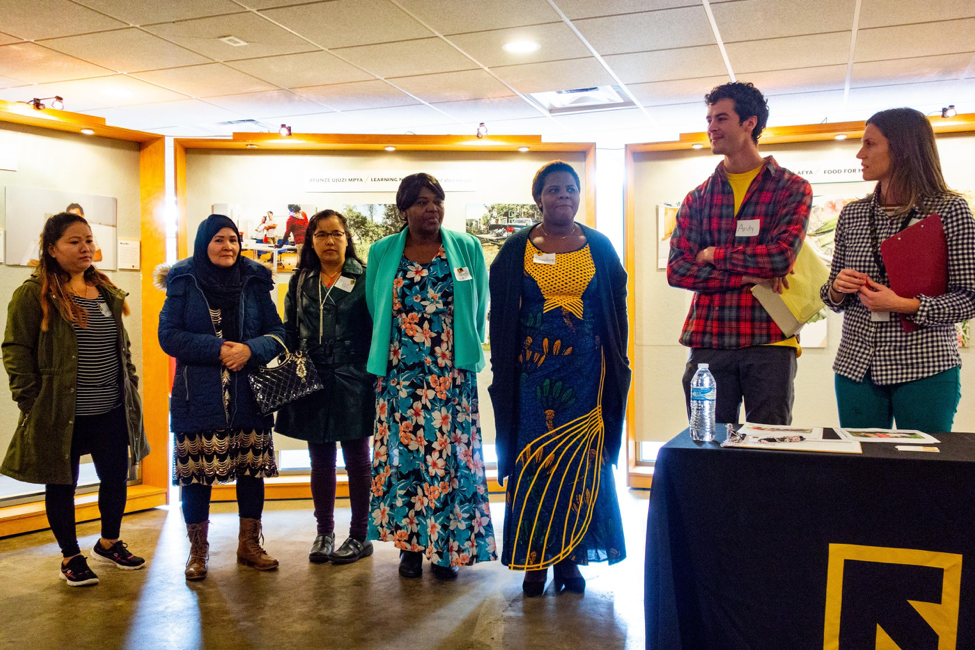 The photographers gather on the 26th of January 2019 to share their work and talk about their photographs with the community.    From left to right: (New Roots and PhotoVoice participants:    Sanchi Gurung    - Bhutan,    Maryam Yousefi    - Afghanistan,    Nar Gurung    - Bhutan,    Elizabeth Ndolo    - Republic of Congo,    Josephine Kanyamukenge    - Democratic Republic of Congo,    Andy Blunk    - New Roots Farm Assistant,    Brooke Ray    - Senior Manager, Food and Agriculture Programs at International Rescue Committee)