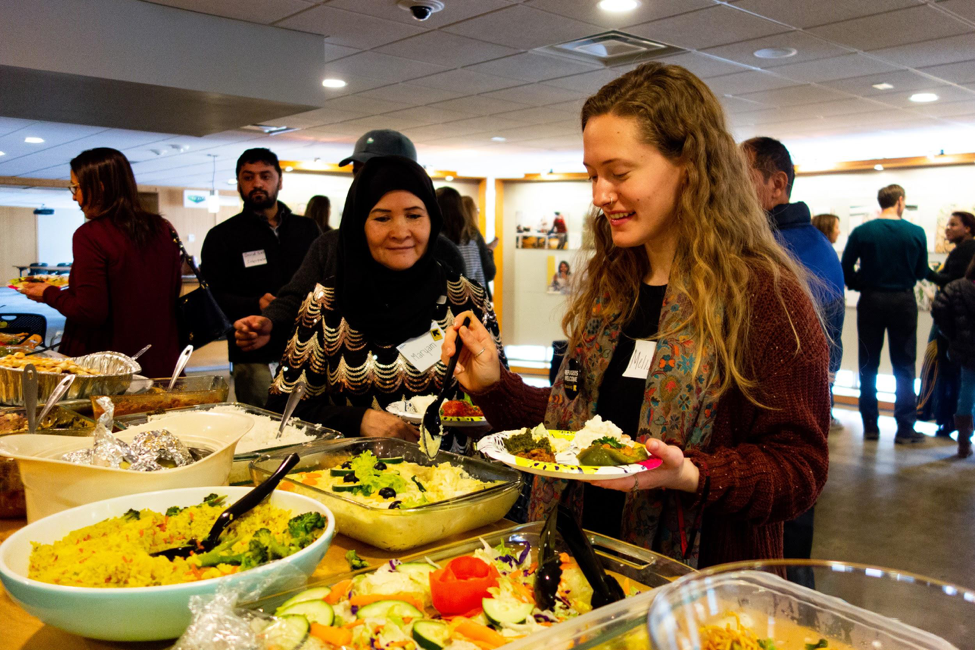 Maryam Yousefi ( New Roots and PhotoVoice Participant )   and   Melissa Katz ( CLAS '19 )   sample food cooked by the participants, representing cuisines from Afghanistan, Bhutan, and the Democratic Republic of Congo.