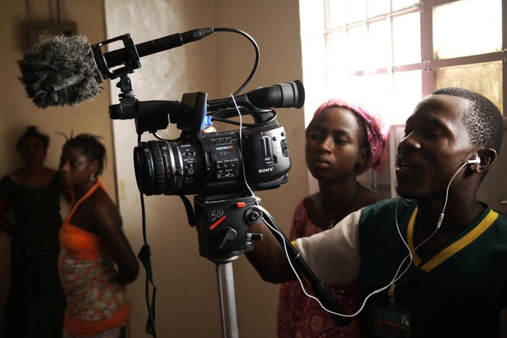Abu Zed directs the camera as Kanku observes.