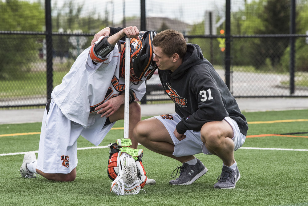 RIT's Chris Becker (31, right) comforts teammate Quinn Commandant (12) after the Tigers' loss in the Semifinal Round of the 2018 NCAA Division III Men's Lacrosse Championship against Wesleyan University on Sunday, May 20 at the RIT Turf Field in Henrietta, N.Y. The Game was RIT's only loss of the season with a score of 19-18.