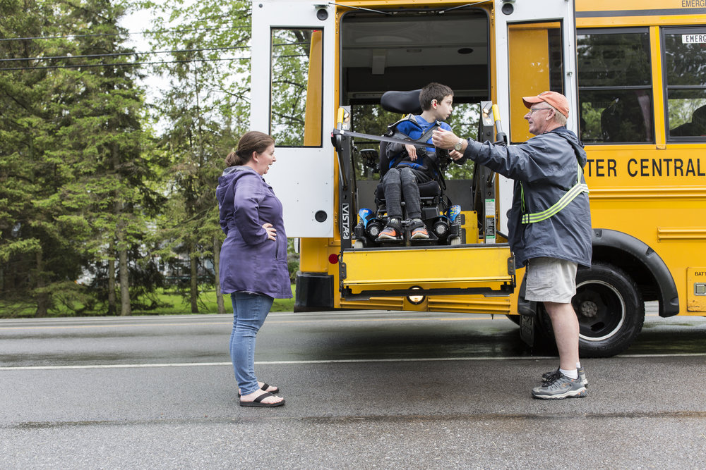 Jamie Nodine talks with Josh's bus driver, Ed, as Joshua, 10, gets on the school bus by their house in Webster, N.Y.