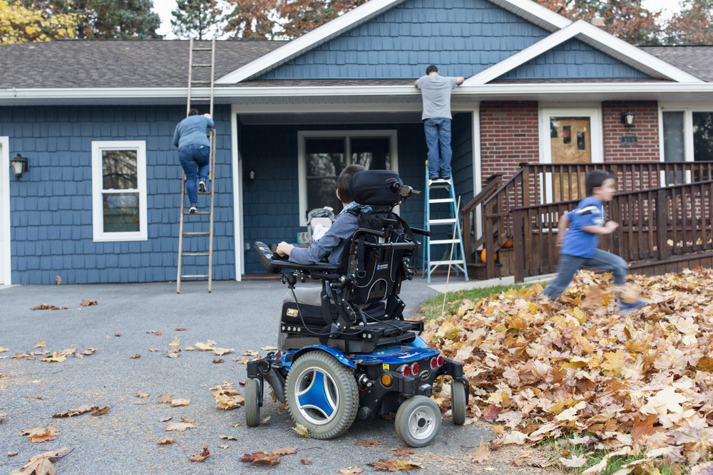 Joshua Nodine, 8, watches as his parents set up Christmas lights and his brother, Caleb, 6, runs into a leaf pile on Nov. 18, 2016.