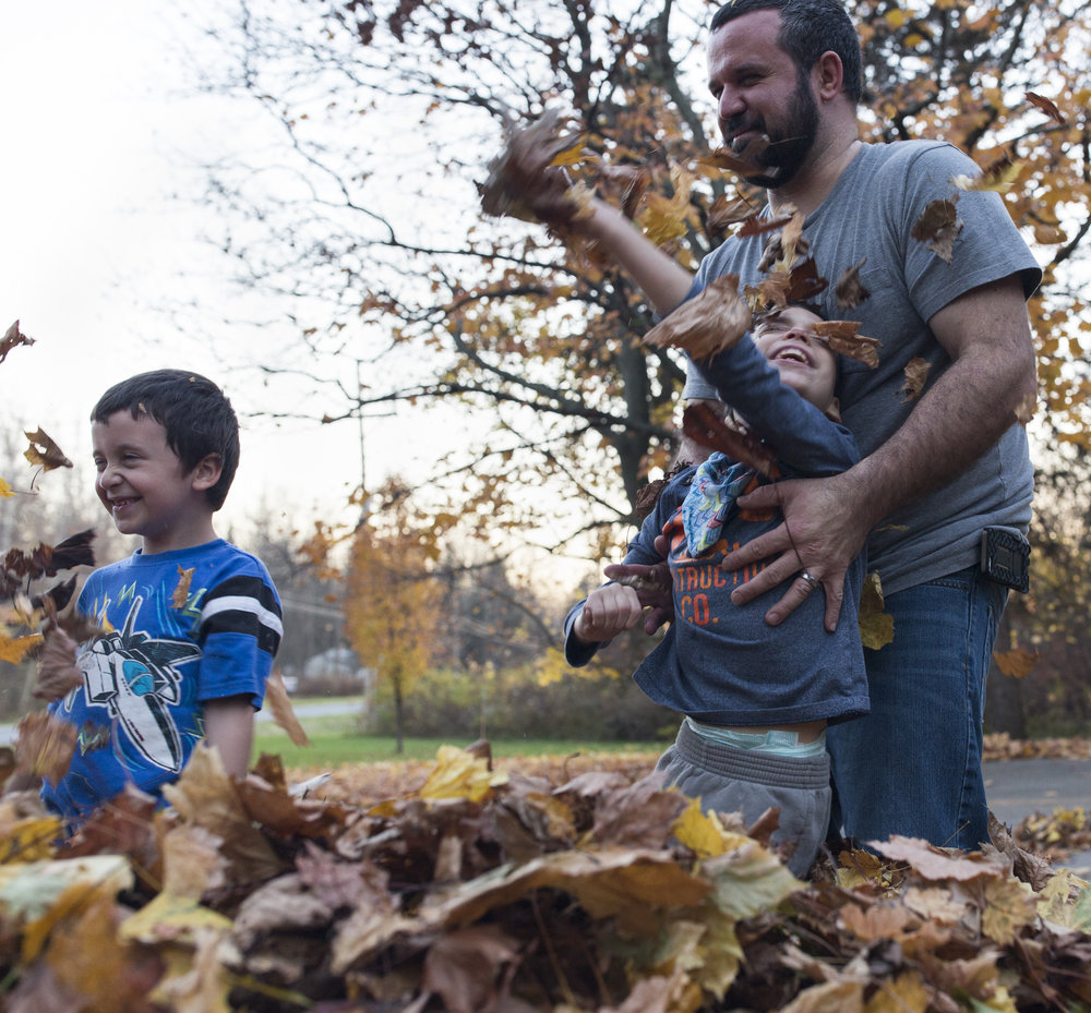 Ben (right) holds up his son Joshua, 8, as he and his brother Caleb, 6, play in a leaf pile outside their home on Nov. 18, 2016.