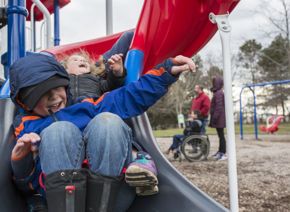 Caleb, 7, and his cousins go down a slide during Josh's (right) tenth birthday party on April 2, 2018.
