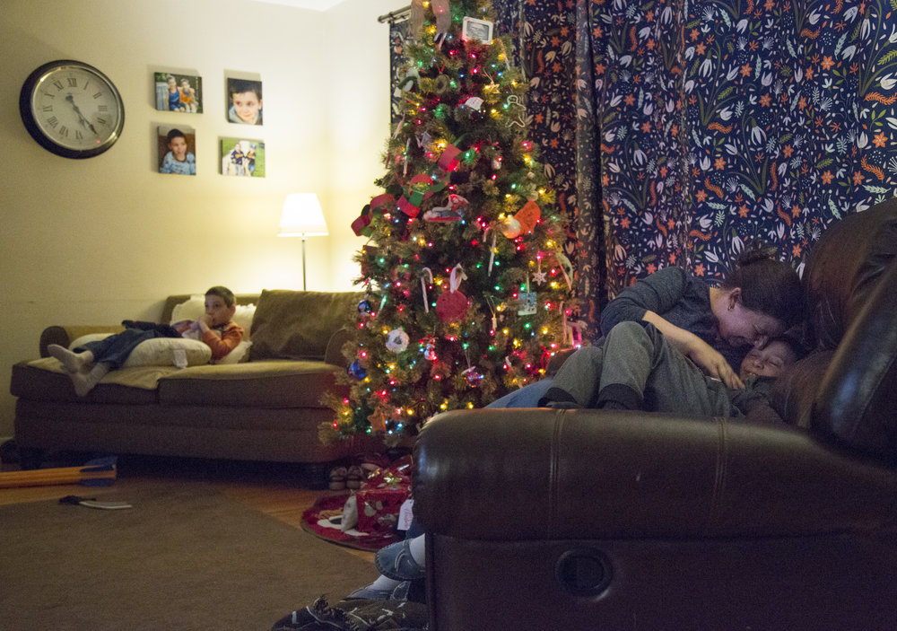 Jamie and her son Caleb (right), 7, cuddle in their home on Dec. 13, 2017. The family tries to make sure that Caleb gets individual attention whenever they can since they often have to focus on Josh.
