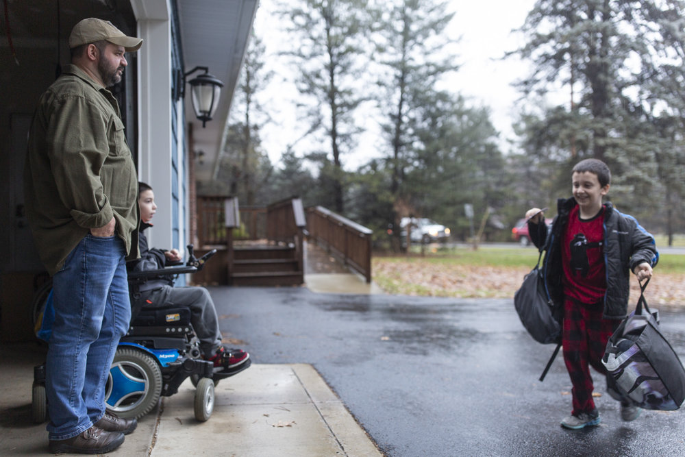Caleb, 8, right, arrives home from school and is greeted by his father, Ben, and brother, Josh, 10 on Dec. 21, 2018. Caleb and Josh attend different schools.