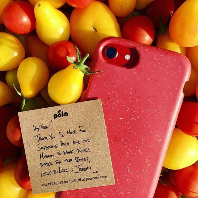 Red phone case in front of bunch of bright yellow and red tomatoes