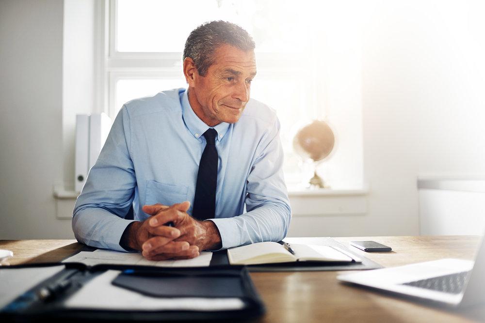 mature-businessman-sitting-in-an-office-working-2HNUK7Q.jpg