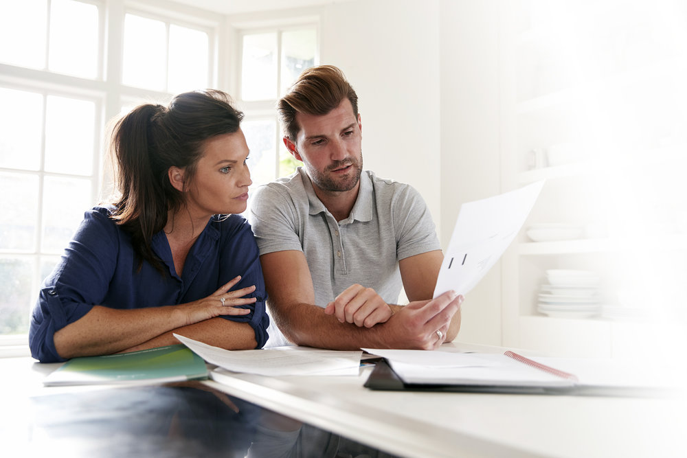 couple-looking-at-domestic-finances-at-home-PK3A2MW.jpg
