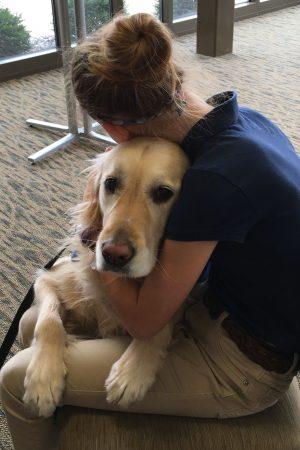 an Emmanuel – St. Michael student hugs a Comfort Dog