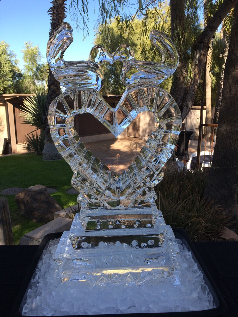 Two kissing love birds perched on a heart shaped full block carving, set up with crushed ice at the base for an impressive presentation
