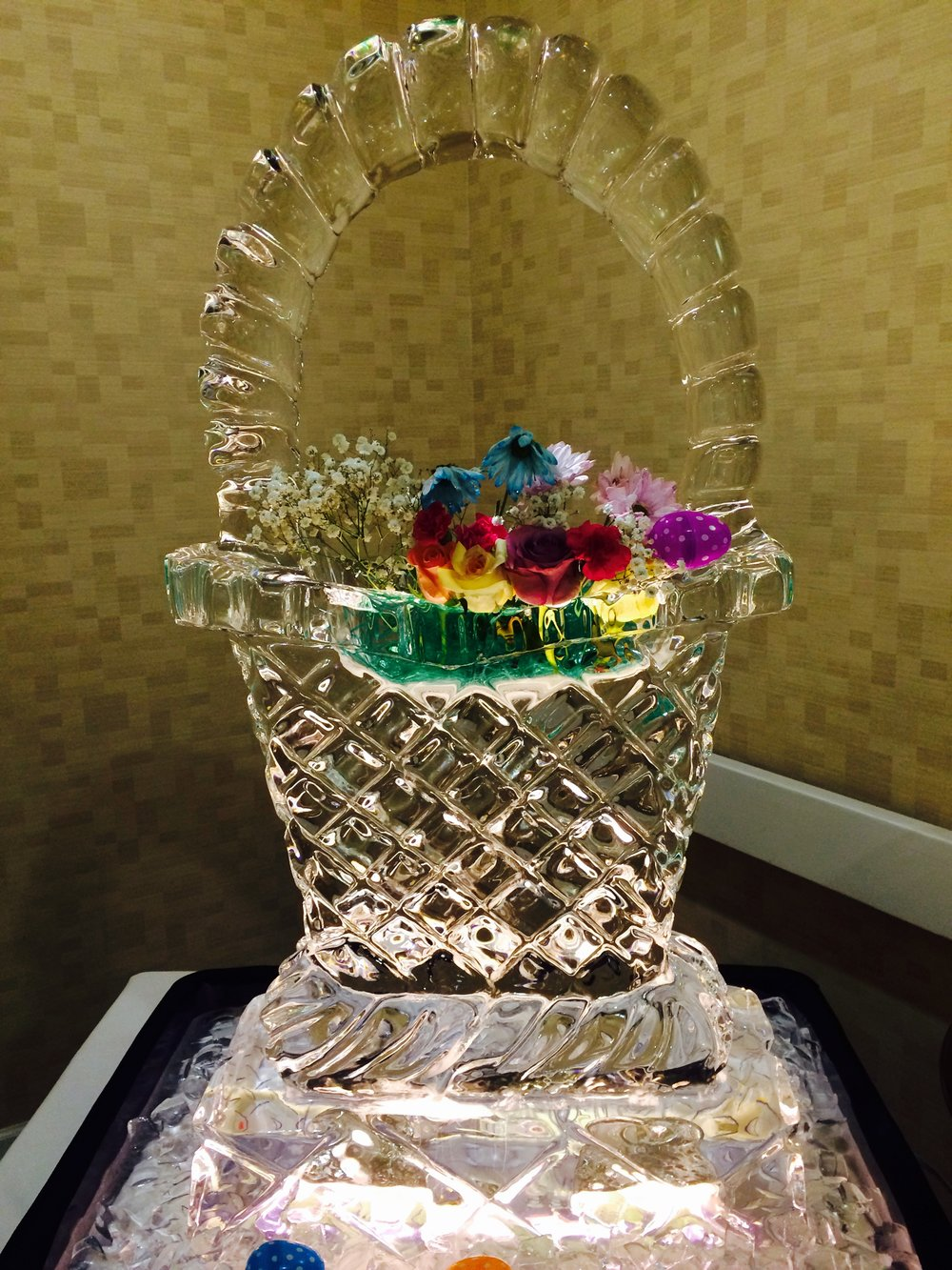 This holiday basket decorated with ornamental flowers was a focal point for an Easter buffet.  Faithfully replicating the basket weave is a form or ice art.