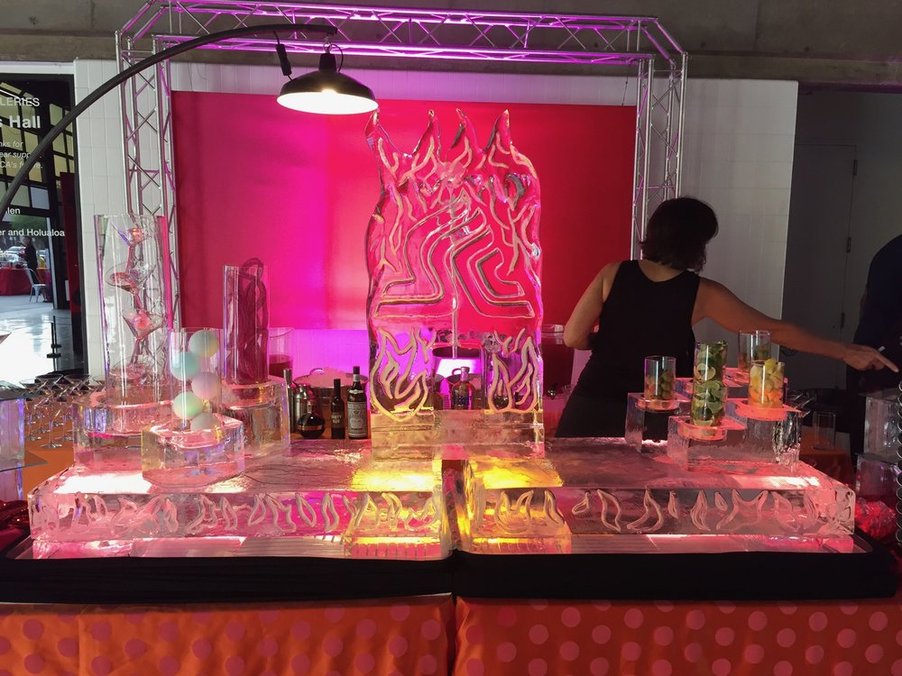 Part of a larger set up, this drink luge, with flames carved into it, has been fitted with up lights to give it a fire-like glow.  It is sitting on an ice table